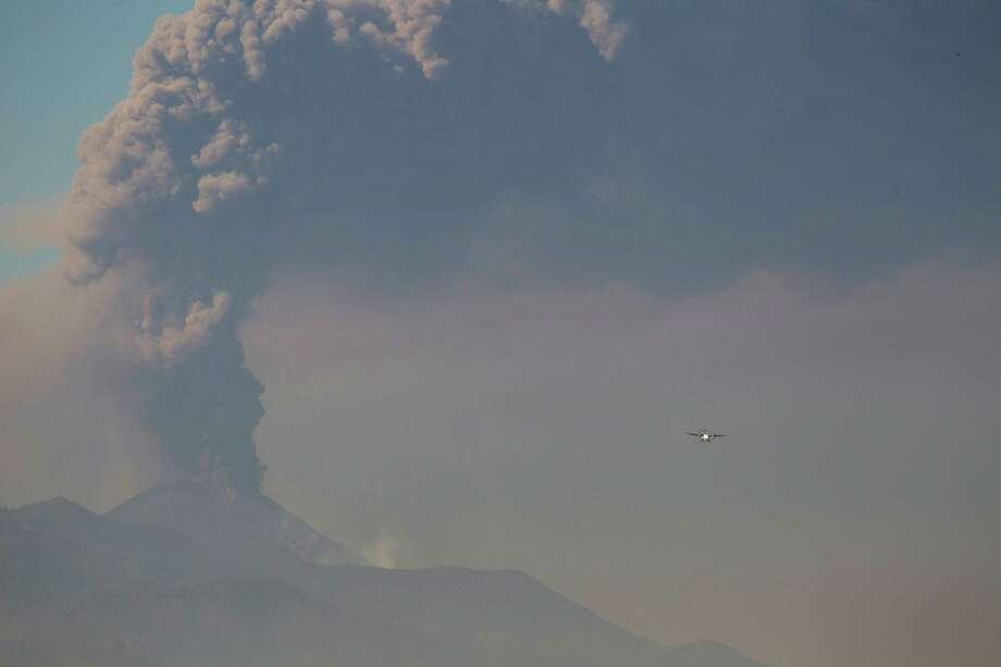 A light aircraft flies towards La Aurora airport in Guatemala City  as the Pacaya Volcano spews ash,  Sunday, March 2, 2014.  column of ash rises from the Pacaya volcano as seen from Villa Nueva, Guatemala, Sunday, March 2, 2014.  Guatemala authorities say the Pacaya volcano near Guatemala City has shot plumes of ash and vapor 2.3 miles (3.7 kilometers) high, while spewing glowing-hot rock. The eruption early Sunday is the latest round of activity at the scenic volcano located just 30 miles (50 kms) south of Guatemala City. Photo: Moises Castillo, AP / AP