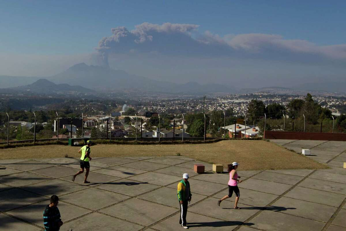 Residents exercise as a column of ash rises from the Pacaya volcano in Villa Nueva, Guatemala, Sunday, March 2, 2014. Guatemala authorities say the Pacaya volcano near Guatemala City has shot plumes of ash and vapor 2.3 miles (3.7 kilometers) high, while spewing glowing-hot rock. The eruption early Sunday is the latest round of activity at the scenic volcano located just 30 miles (50 kms) south of Guatemala City.