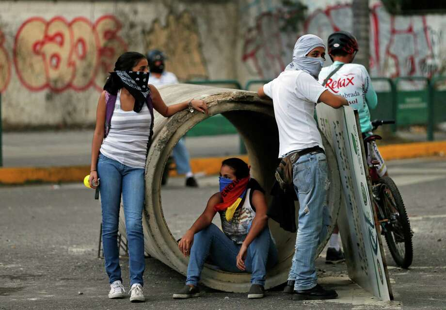 Masked demonstrators block a road with a water pipe during clashes with the Bolivarian National Guard in Caracas, Venezuela, Thursday, Feb. 27, 2014. Anti-government protesters rallied and tried to block a highway to demand an end to the government crackdown on protests and the release of those jailed in recent weeks. Photo: Fernando Llano, AP / AP2014