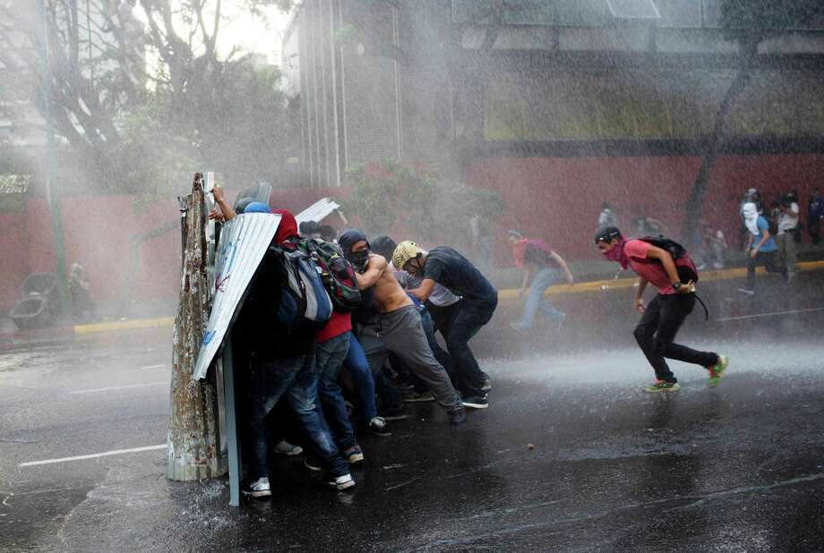 Anti government demonstrators take cover from a police water cannon in Caracas, Venezuela, Friday, Feb. 28, 2014. The start of a weeklong string of holidays leading up to the March 5 anniversary of former President Hugo Chavez's death has not completely pulled demonstrators from the streets as the government apparently hoped. President Nicolas Maduro announced this week that he was adding Thursday and Friday to the already scheduled long Carnival weekend that includes Monday and Tuesday off, and many people interpreted it as an attempt to calm tensions. Photo: Rodrigo Abd, AP / AP