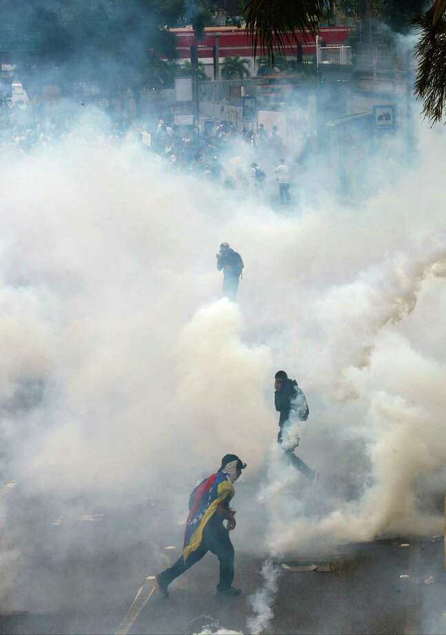 Demonstrators run amid tear gas fired by the Bolivarian National Guard to keep them from blocking a major highway in Caracas, Venezuela, Thursday, Feb. 27, 2014. Anti-government protesters rallied to demand an end to the government crackdown on protests and the release of those jailed in recent weeks. Photo: Fernando Llano, AP / AP2014
