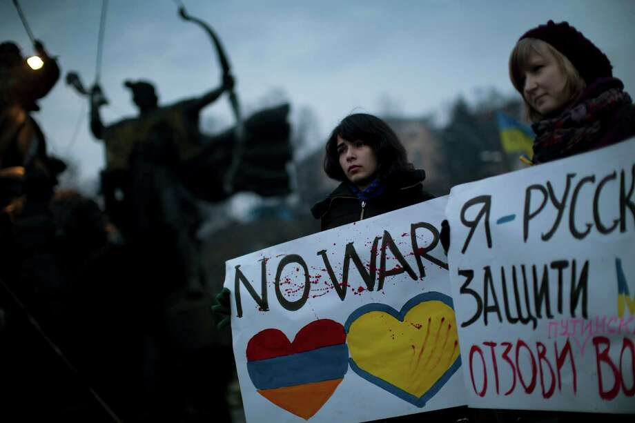 "Ukrainian Maria, 23, right, and Vanui, 22, hold posters against Russia's military intervention in Crimea, in Kiev, Ukraine, Sunday, March 2, 2014. Russia's parliament approved a motion to use the country's military in Ukraine after a request from President Vladimir Putin as protests in Russian-speaking cities turned violent Saturday, sparking fears of a wide-scale invasion. The poster in the right side reads in Ukrainian: ""I am from Russia, please protect me and remove the weapons and soldiers from Ukraine."" Photo: Emilio Morenatti, AP / AP"