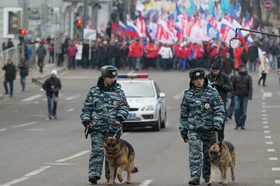 Police officers with dogs walk in front of more than ten thousand pro-Kremlin demonstrators many holding Russian flags march in central Moscow, Russia, Sunday, March 2, 2014 to express support for the latest developments in Russian-Ukrainian relations. Photo: Pavel Golovkin, AP / AP