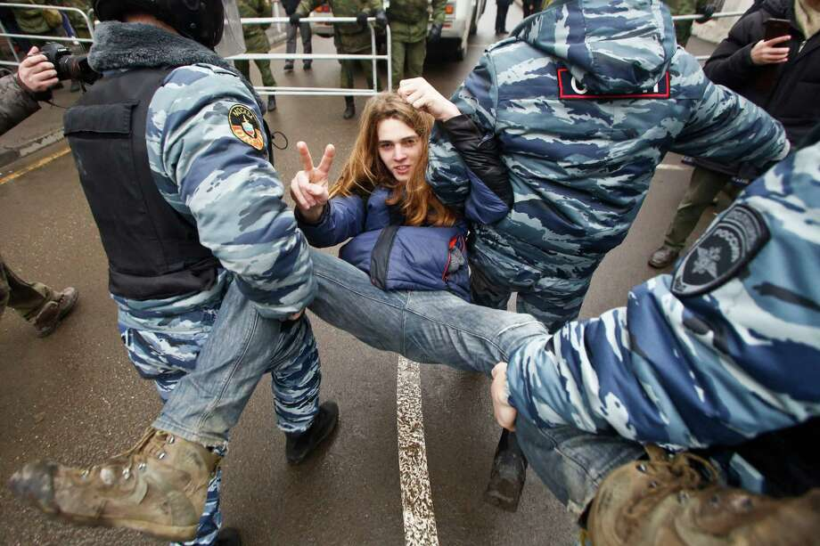 Russian police officers detain an opposition activist outside a court room in Moscow, Russia, Monday, Feb. 24, 2014, where hearings started against opposition activists detained on May 6, 2012 during a rally at Bolotnaya Square. A Moscow judge on Friday, Feb. 21, 2014, convicted eight anti-government protesters of rioting during a 2012 protest against Vladimir Putin, following a trial seen as part of the Kremlin's efforts to stifle dissent. Photo: Denis Tyrin, AP / AP2014