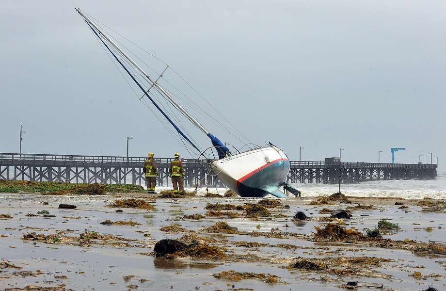Santa Barbara County firefighters survey the scene after three sailboats washed ashore in Goleta, Calif., Saturday, March 1, 2014. The storm marked a sharp departure from many months of drought that has grown to crisis proportions for the state's vast farming industry. However, such storms would have to become common to make serious inroads against the drought, weather forecasters have said. Photo: Mike Eliason, AP / AP2014