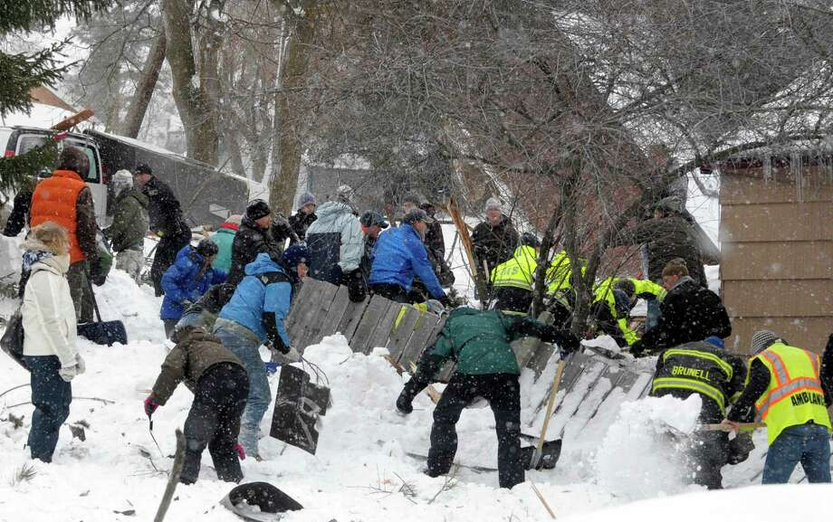 Rescuers dig frantically at the scene of an avalanche in Missoula's Rattlesnake Valley on Friday, Feb. 28, 2014, looking for a boy buried in the snow. The avalanche roared into a residential neighborhood and destroyed a house, but three people were found alive amid the snow and wreckage, police said. The survivors were an elderly couple and an 8-year-old boy, police Sgt. Travis Welsh said. Photo: Tom Bauer, AP / AP2014
