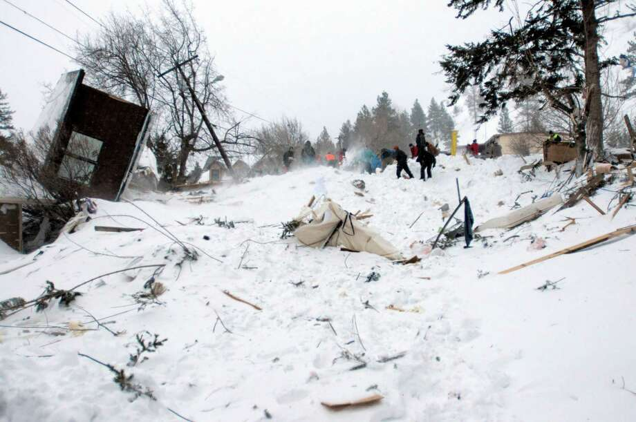 Rescuers dig at the scene of an avalanche in Missoula's Rattlesnake Valley on Friday, Feb. 28, 2014. The avalanche roared into a residential neighborhood and destroyed a house, but three people were found alive amid the snow and wreckage, police said. The survivors were an elderly couple and an 8-year-old boy, police Sgt. Travis Welsh said. Photo: Tom Bauer, AP / AP2014