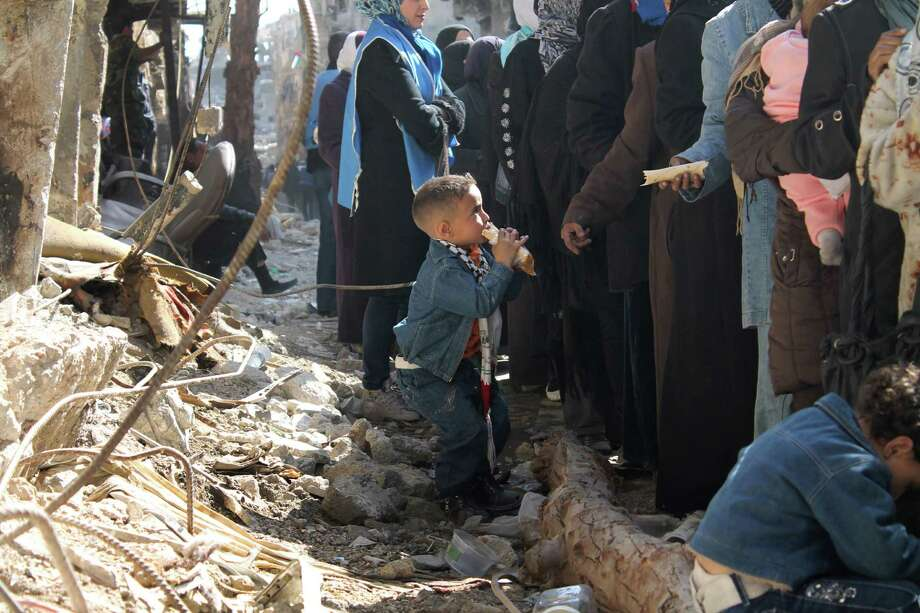 In this picture taken on Monday Feb. 24, 2014, and released by the United Nations Relief and Works Agency for Palestine Refugees in the Near East (UNRWA), residents of the besieged Palestinian camp of Yarmouk stand in line to receive sandwiches distributed by UNRWA, in Damascus, Syria. U.N. Secretary General Ban Ki-Moon urged Syrian government to authorize more humanitarian staff to work inside the country, devastated by its 3-year-old conflict. Photo: Uncredited, AP / UNRWA