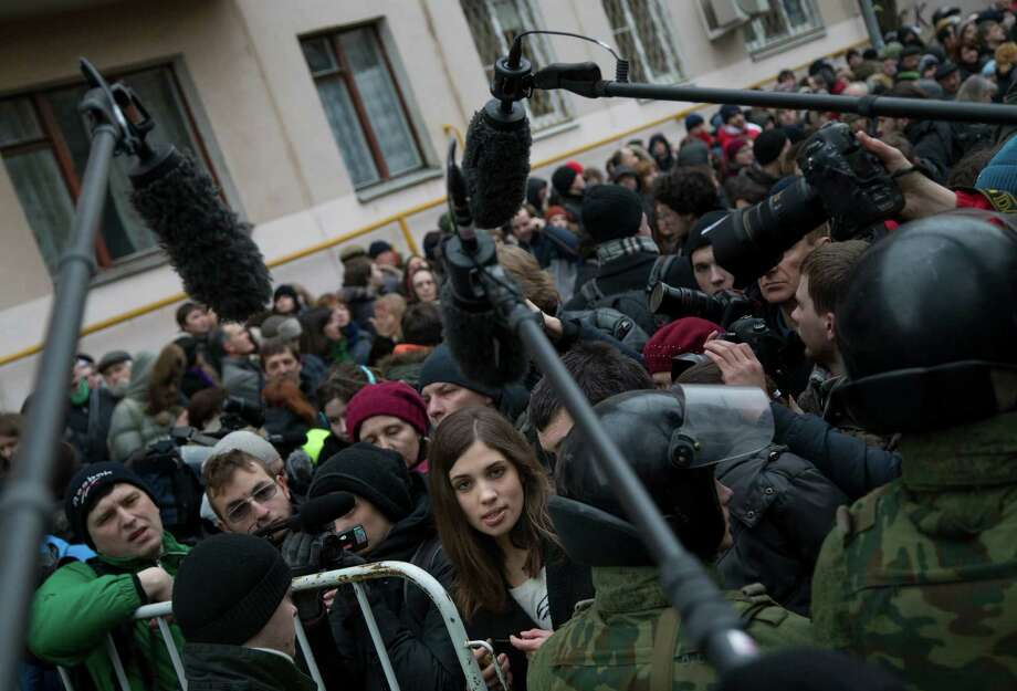 Member of the Pussy Riot punk group, Nadezhda Tolokonnikova, center,  surrounded by journalists, stands in front of police line outside Zamoskvoretsky District Court in Moscow, Russia, Monday, Feb. 24, 2014, where hearings started against opposition activists detained on May 6, 2012 during the rally at Bolotnaya Square. A Moscow judge on Friday, Feb. 21, 2014, convicted eight anti-government protesters of rioting during a 2012 protest against Vladimir Putin, following a trial seen as part of the Kremlin's efforts to stifle dissent. Photo: Alexander Zemlianichenko, AP / AP2014