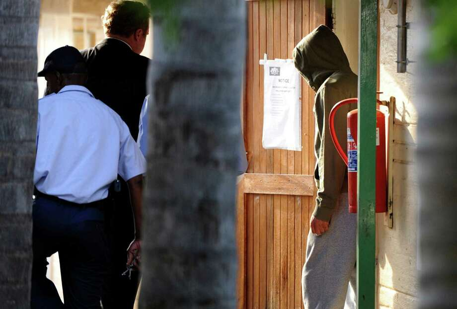 In this file photo taken Feb, 14, 2014 Olympic athlete Oscar Pistorius, right, heads to the holding cells at the Boschkop police station, east of Pretoria, South Africa. Pistorius goes on trial Monday, March 3, 2014 for the shooting death of his girlfriend Reeva Steenkamp. Prosecutors pressing the murder charge have listed 107 witnesses they're able to call and some will say that the world-famous athlete had a fight with  Steenkamp and then intentionally killed her. Photo: Str, AP / AP