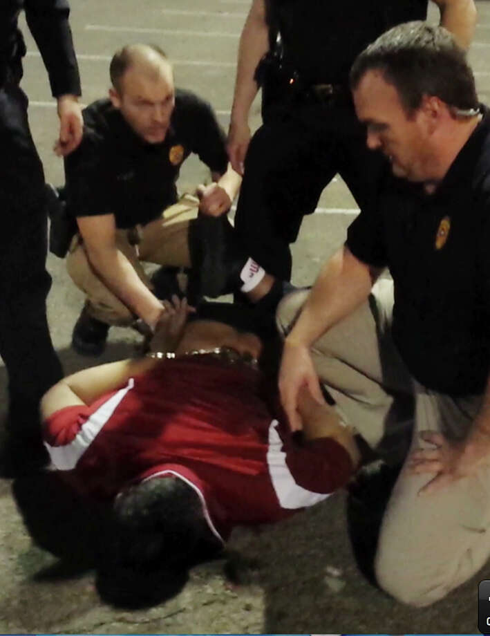 In a frame grab from a Saturday, Feb. 15, 2014 cellphone video provided by Nair Rodriguez, Luis Rodriguez, lying face down on the ground, is handcuffed after being subdued by five police officers in Moore, Okla. Rodriguez died following the altercation with police. Photo: Nair Rodriguez, AP / Nair Rodriguez