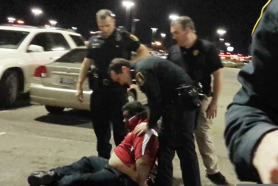 In a frame grab from a Saturday, Feb. 15, 2014 cellphone video provided by Nair Rodriguez, Luis Rodriguez sits with his hands handcuffed behind him after being subdued by five police officers outside a movie theater in Moore, Okla. Rodriguez died following the altercation with police. Photo: Nair Rodriguez, AP / AP2014
