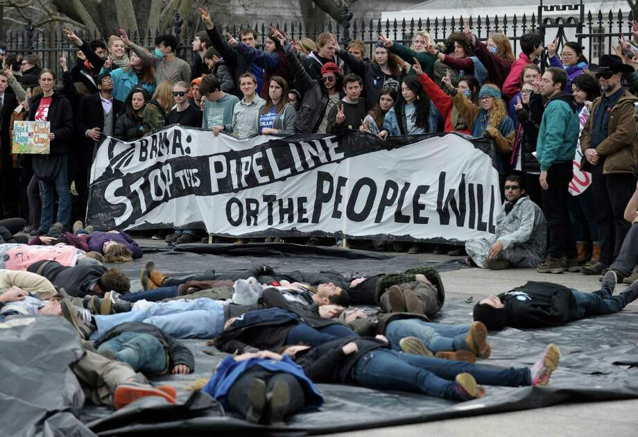 Several hundred students and youth who marched from Georgetown University to the White House to protest the Keystone XL Pipeline wait to be arrested outside the White House in Washington, Sunday, March 2, 2014. Photo: Susan Walsh, AP / AP