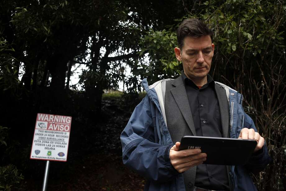 "Jesper Jurcenoks uses an iPad to check the surveillance system in his Oakland hills neighborhood. ""We will not a let a criminal enter or leave our neighborhood undetected,"" Jurcenoks, founder of the nonprofit Neighborhood Guard, says of the surveillance system. Photo: Lacy Atkins, The Chronicle"