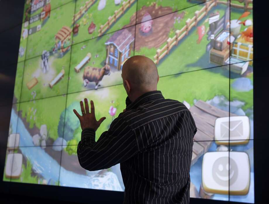 "Jonathan Knight demos a new mobile version of ""FarmVille"" at a staff meeting for employees at Zynga headquarters. Photo: Paul Chinn, The Chronicle"