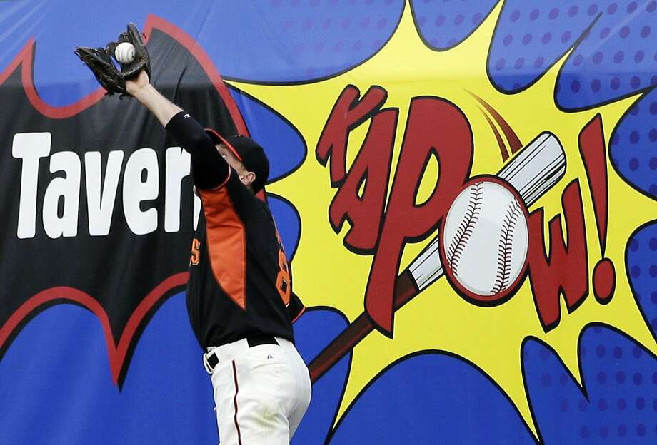 Somewhere among all the signage on the outfield wall at Scottsdale Stadium, right fielder Hunter Pence is running down a flyball hit by the Diamondbacks' Didi Gregorius. Photo: Gregory Bull, Associated Press