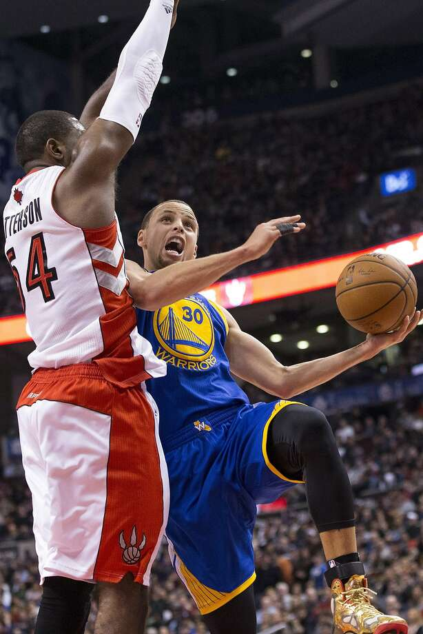 Stephen Curry, who scored a game-high 34 points, attempts to get off a shot as Toronto's Patrick Patterson defends. Curry added seven assists but committed six turnovers. Photo: Chris Young, Associated Press