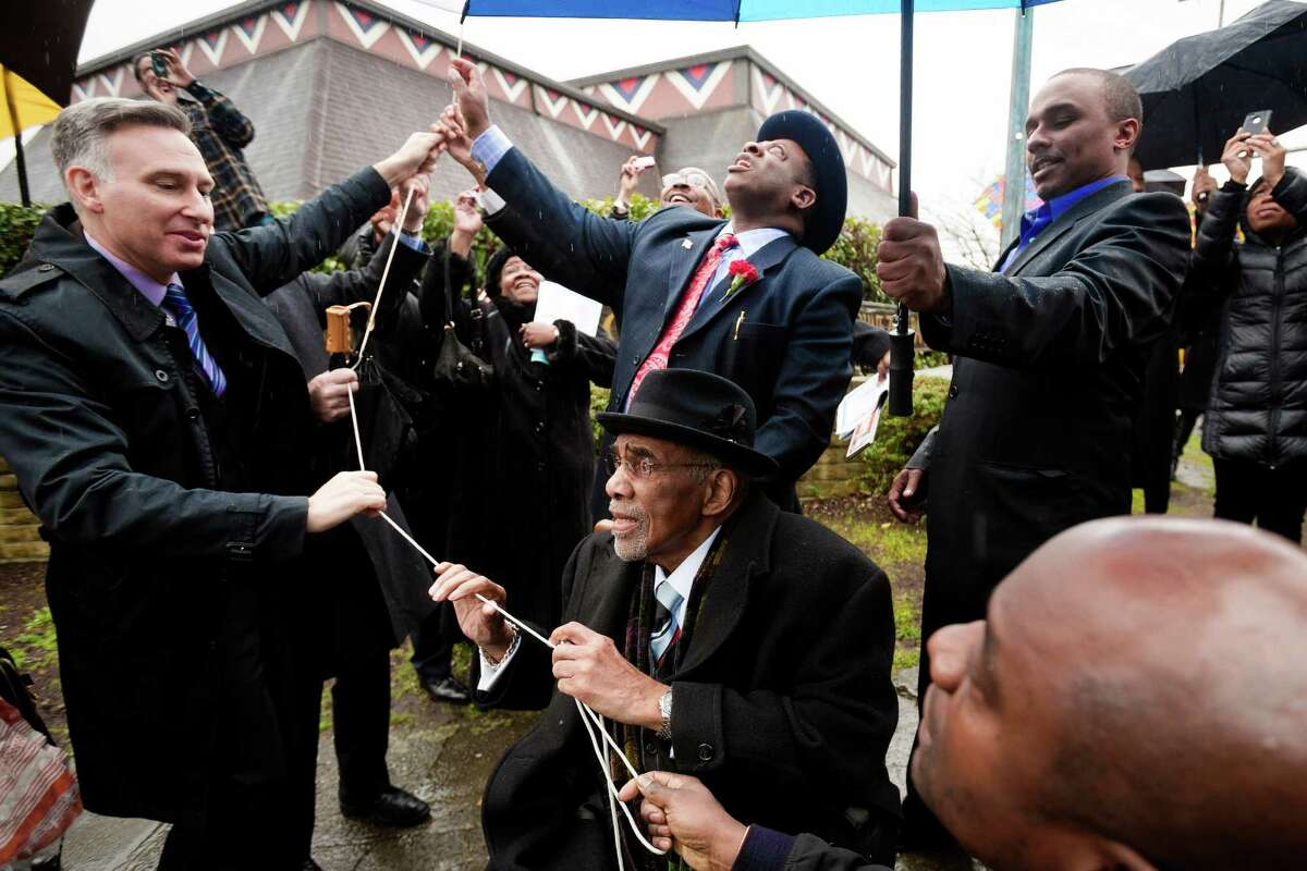Living legend and leader in the movement for human rights, Rev. Dr. Samuel B. McKinney, bottom center, does his part in pulling the string on the unveiling of the Rev. Dr. S. McKinney Avenue honorary street sign Sunday, March 2, 2014, at Mt. Zion Baptist Church in Seattle. A portion of 19th Avenue will now be known as Rev. Dr. S. McKinney Ave.