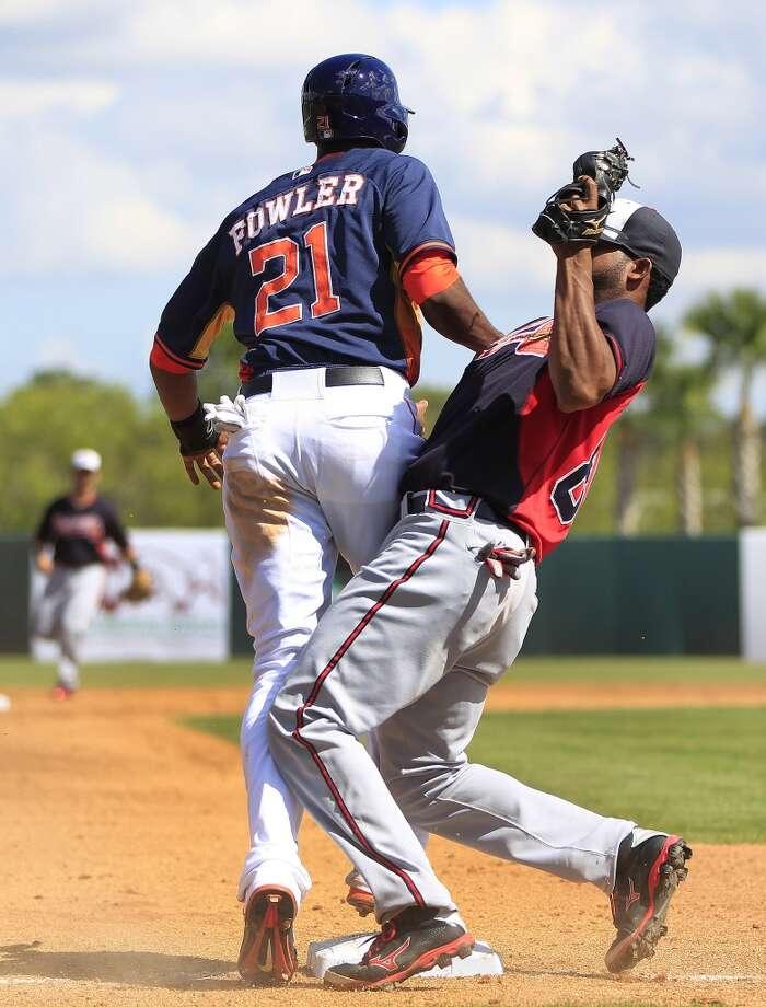Dexter Fowler and Atlanta's Edward Salcedo collide at third base in the third inning. Photo: Karen Warren, Houston Chronicle