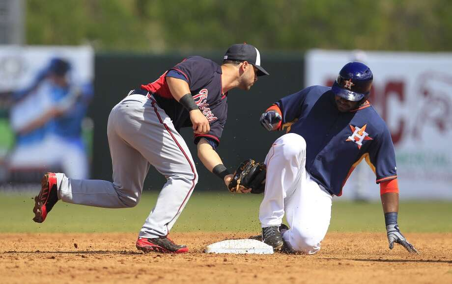 Chris Carter slides into second on a double as Atlanta's Tommy La Stella tries to tag him in the third inning. Photo: Karen Warren, Houston Chronicle