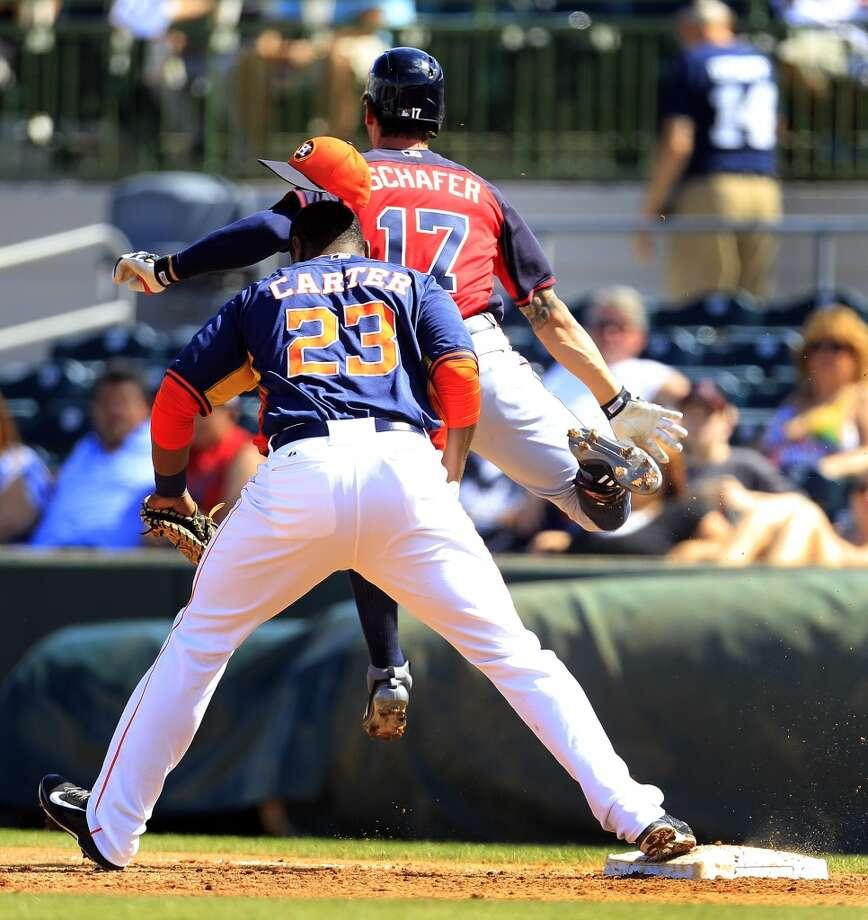 Atlanta's Jordan Schafer knocks the hat off of Chris Carter as he grounded out at first base. Photo: Karen Warren, Houston Chronicle