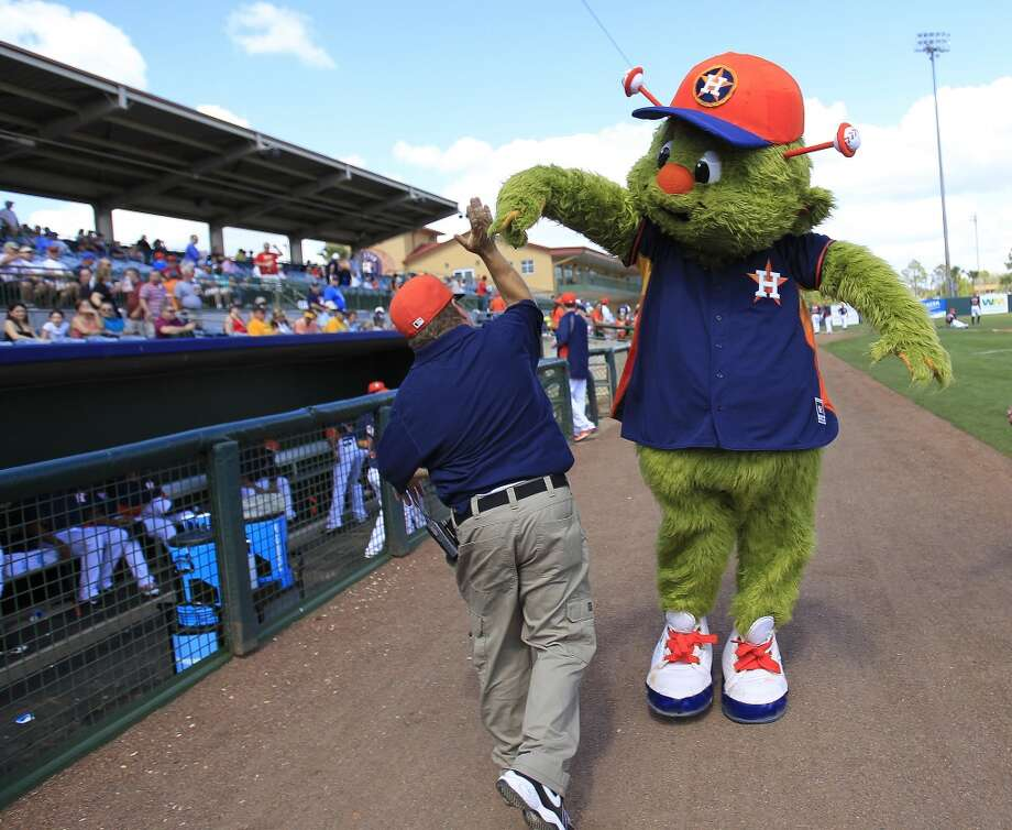 Orbit high fives Tracy Neal before the start of the game. Photo: Karen Warren, Houston Chronicle
