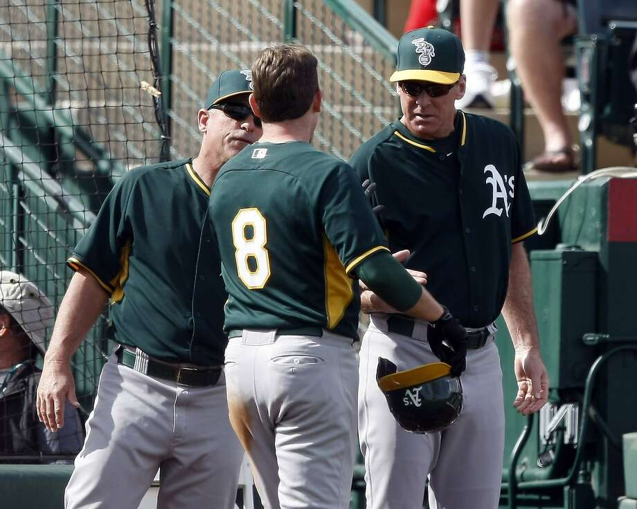 Manager Bob Melvin extends a celebratory hand to Jed Lowrie (8) after Lowrie scored one of his two runs against the Angels. Photo: Rick Scuteri, Reuters