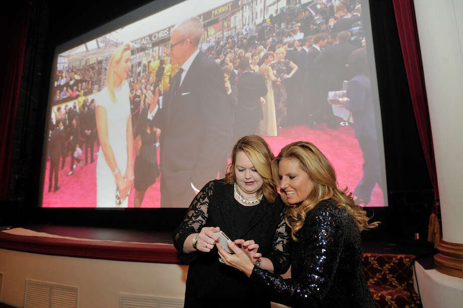 Danelle Aune, left, and Eleni Sotiriou look at a photo they took in front of the screen as Naomi Watts is interviewed in real-time on the red carpet during the Avon Oscar Night Party at the Avon Theatre in Stamford, Conn., on Sunday, March 2, 2014. Photo: Jason Rearick / Stamford Advocate