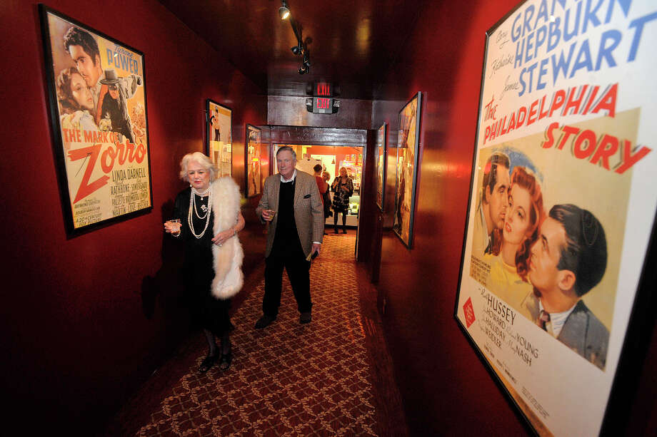 Gail Kirhoffer and her date, Stu Reider, walk past movie posters to get to the theater that is showing the Oscars during the Avon Oscar Night Party at the Avon Theatre in Stamford, Conn., on Sunday, March 2, 2014. People were asked to come dressed in period attire from 1939, the year the Avon Theatre opened on Bedford Street in Stamford. Photo: Jason Rearick / Stamford Advocate