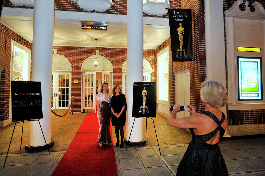 Jackie Wetenhall, right, photographs Linda Kuppersmith, left, and Gail Welch in front of the Avon Theatre during the Avon Oscar Night Party in Stamford, Conn., on Sunday, March 2, 2014. Photo: Jason Rearick / Stamford Advocate