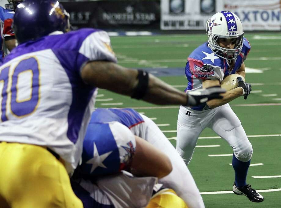 Jennifer Welter runs up the field as the North Texas Crunch defense closes in during an Indoor Football League game last month in Allen in North Texas. Welter, 36, says she has always loved football and jumped at the chance to play in the IFL. The running back says her teammates accept her now. Photo: Photos By Vernon Bryant / Associated Press / TThe Dallas Morning News