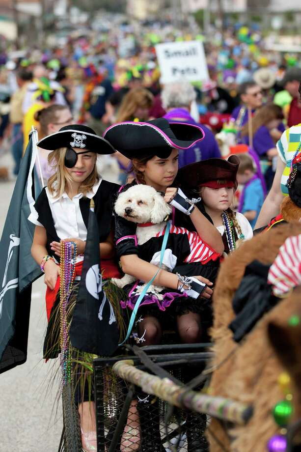 At left, Jordan Davis, 8, Elena Foulks, 9, her dog Salty and Luna Paessler, 4, prepared to throw beads as hundreds of pets and their owners paraded down the Seawall during the Krewe of Barkus & Meoux Parade, one of many parades during  Mardi Gras! Galveston festivities Sunday, March 2, 2014, in Galveston.  The Galveston Island Humane Society began the Krewe of Barkus and Meoux Parade in 1998 as a way to involve the community in the spirit of Mardi Gras and feature their family pets. Photo: Johnny Hanson, Houston Chronicle / © 2014  Houston Chronicle