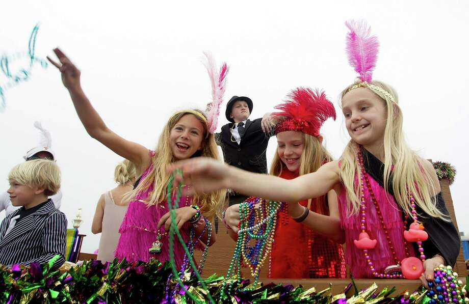 Children on The Great Gatsby float including, at left, Alex Vasut, 10, Miles Lebouf, 12, Noa Seigel, 9, and Sara Gabriel, 10, throw beads along the Seawall during the Mardi Gras Children's Parade, one of many parades during  Mardi Gras! Galveston festivities Sunday, March 2, 2014, in Galveston. Photo: Johnny Hanson, Houston Chronicle / © 2014  Houston Chronicle