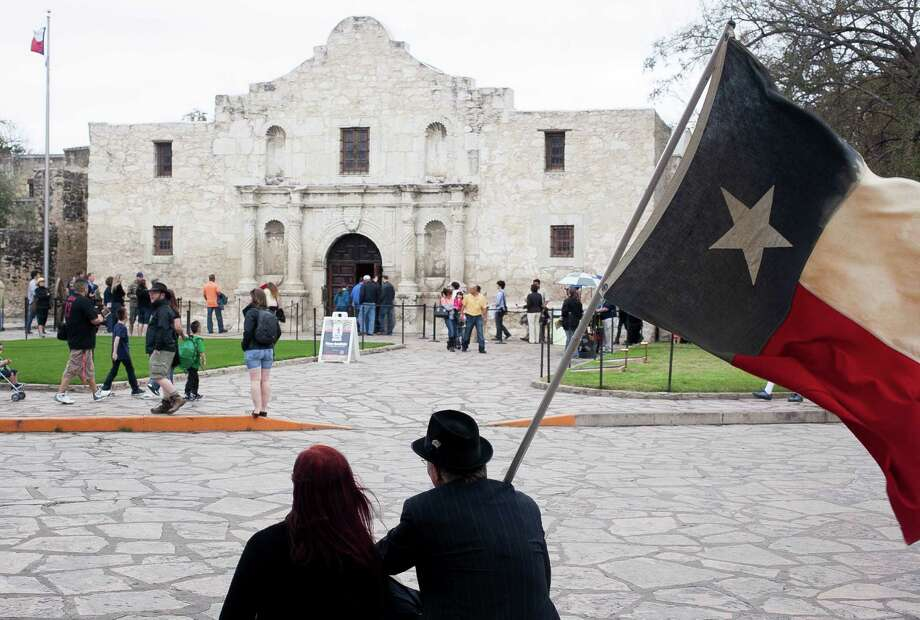 Don and Vikie Schwartz wave their Texas flag in front of the Alamo on Sunday afternoon. A short ceremony marked the 178th anniversary of the signing of the Declaration of Texas Independence. Photo: Photos By Julysa Sosa / For The San Antonio Express-News / Julysa Sosa/ San Antonio Express-News