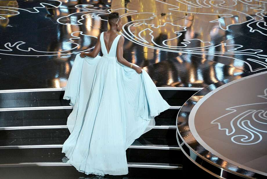 Best supporting actress Lupita Nyong'o creates drama in a pale blue sweep of Prada. Photo: Kevin Winter, Getty Images