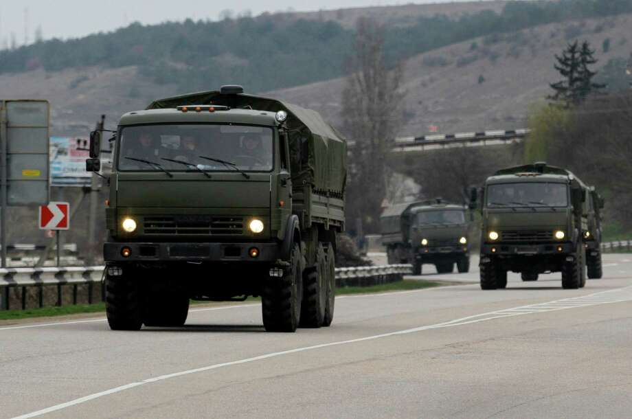 A Russian convoy moves from Sevastopol to Sinferopol in the Crimea, Ukraine, Sunday, March 2, 2014. A convoy of hundreds of Russian troops headed toward the regional capital of Ukraine's Crimea region on Sunday, a day after Russia's forces took over the strategic Black Sea peninsula without firing a shot. The new government in Kiev has been powerless to react. Ukraine's parliament was meeting Sunday in a closed session. (AP Photo/Darko Vojinovic) Photo: Darko Vojinovic, STF / AP