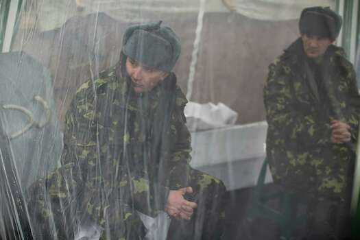 Anti-Yanukovych protesters sit inside a tent as they guard one of the entrance in Kiev's Independence Square, the epicenter of the country's current unrest, Ukraine, Sunday, March 2, 2014. A convoy of hundreds of Russian troops is heading toward the regional capital, Simferopol on the Crimean peninsula in Ukraine today. On the road from Sevastopol, the Crimean port where Russia maintains a naval base, AP journalists saw 12 military trucks. Russian troops took over the strategic Black Sea peninsula yesterday and are ignoring international protests. (AP Photo/Emilio Morenatti) Photo: Emilio Morenatti, STF / AP