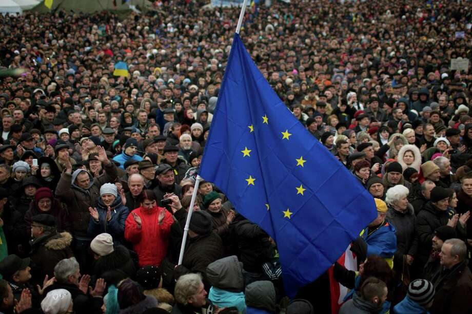 "People applaud as the European Union flag held by a protester arrives at the Independence square during a rally in Kiev Ukraine, Sunday, March 2, 2014. Ukraine's new prime minister urged Russian President Vladimir Putin to pull back his military Sunday in the conflict between the two countries, warning that ""we are on the brink of disaster."" The comments from Arseniy Yatsenyuk came as a convoy of Russian troops rolled toward Simferopol, the capital of Ukraine's Crimea region, a day after Russian forces took over the strategic Black Sea peninsula without firing a shot. (AP Photo/Emilio Morenatti) Photo: Emilio Morenatti, STF / AP"
