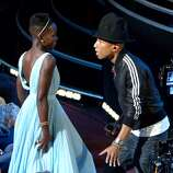 "Lupita Nyong'o, left, dances along with Pharrell Williams during his performance of ""Happy"" at the Oscars at the Dolby Theatre on Sunday, March 2, 2014, in Los Angeles."