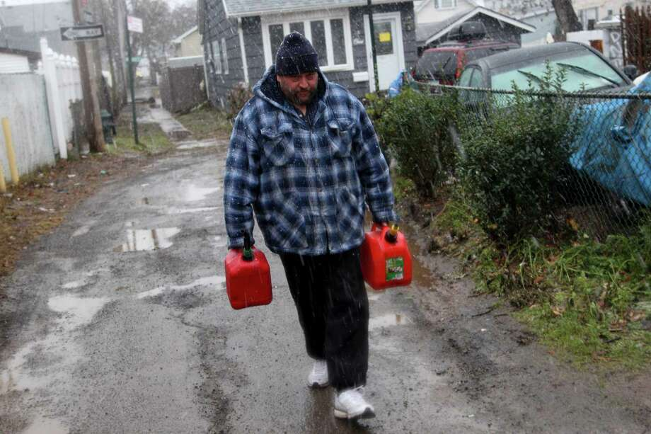 Joe Graham delivers some gas in the snow to a neighbor for use in her generator in the New Dorp section of Staten Island, N.Y. Wednesday, Nov. 7, 2012.  A nor'easter blustered into New York and New Jersey on Wednesday, threatening to swamp homes all over again, plunge neighborhoods back into darkness and inflict more misery on tens of thousands of people still reeling from Superstorm Sandy.  (AP Photo/Seth Wenig) Photo: Seth Wenig / AP