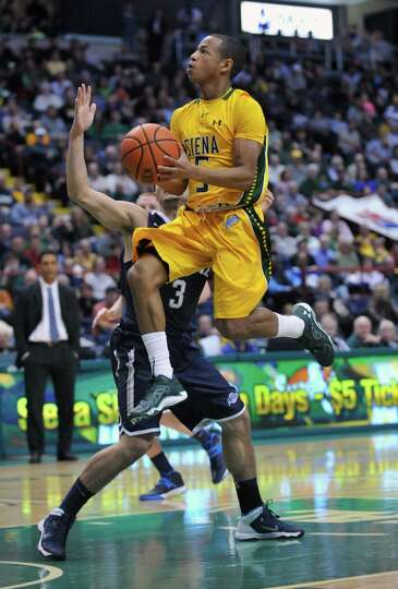 Siena's Evan Hymes (5) scores againt Monmouth during the first half of an NCAA college basketball in