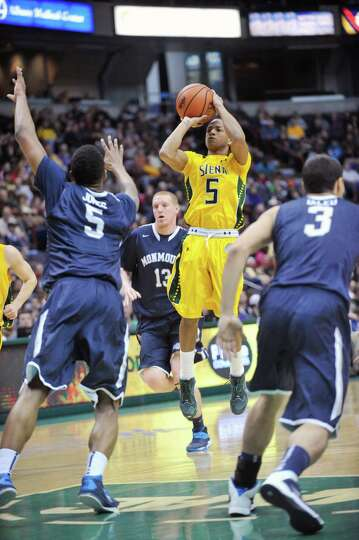 Siena's Evan Hymes (5) puts up a shot against Monmouth during the first half of an NCAA college bask