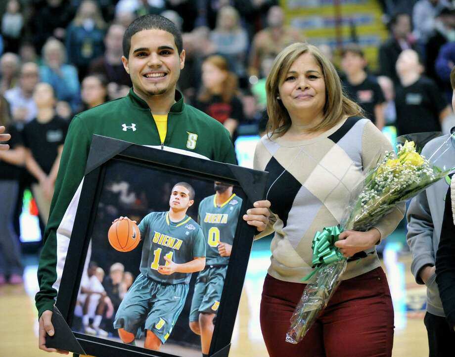Siena senior Steven Cruz, left, stands with his mother Ani Cruz as he is  honored during a pregame ceremony, prior to a NCAA college basketball game against Monmouth in Albany, N.Y., Sunday, March 2, 2014. (Hans Pennink / Special to the Times Union) ORG XMIT: HP115 Photo: Hans Pennink / Hans Pennink