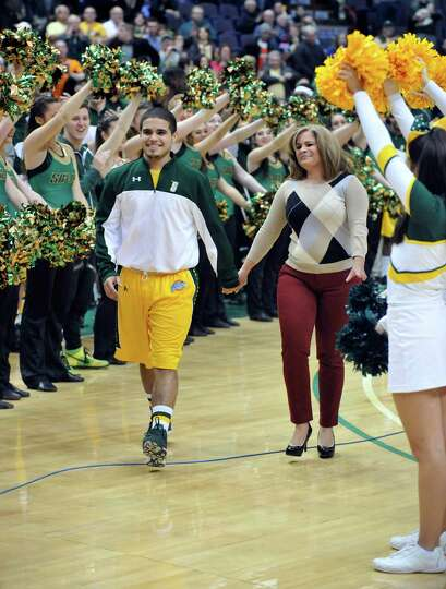 Siena senior Steven Cruz, left, walks with his mother Ani Cruz as he is  honored during a pregame ce