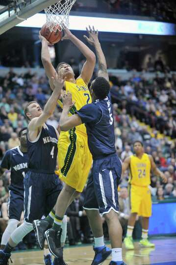 Siena's Javion Ogunyemi (2) puts up a shot against Monmouth during the first half of an NCAA college