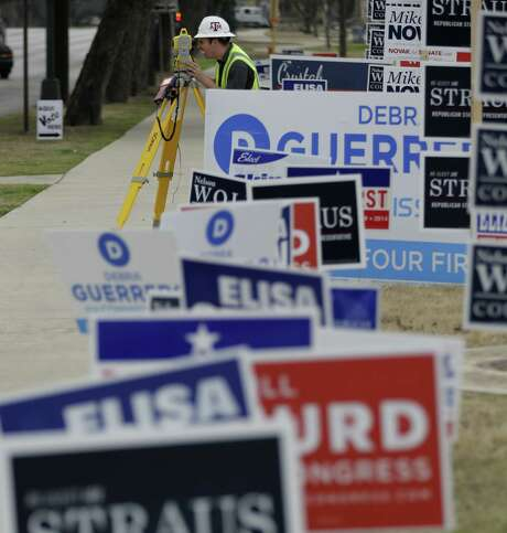 A worker and his surveying equipment stand near campaign signs at an early voting site last month. Early voter turnout in Bexar County for the primary elections was a modest 6.5 percent. Tuesday's elections feature plenty of state and local races. Photo: Eric Gay / Associated Press / AP