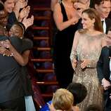 "Steve McQueen, left, and Lupita Nyong'o celebrate in the audience after ""12 Years a Slave"" is announced as winner of the award for best picture of the year during the Oscars at the Dolby Theatre on Sunday, March 2, 2014, in Los Angeles."