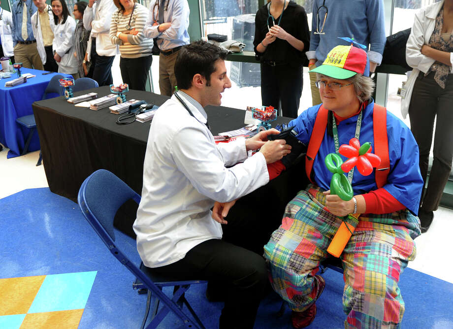 Quinnipiac Physician's Assistant student Robert Franceskino checks Debbie Perry's blood pressure, while she takes a break from clowning around, at St. Vincent's Hospital's annual Healthy Heart Fair at the Webster Bank Arena in Bridgeport, Conn. on Saturday February 15, 2014. This year the hospital teamed up with Fairfield University's Stags Men's Basketball Team to offer important health information to basketball fans. Photo: Christian Abraham / Connecticut Post