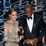 Actors Angelina Jolie (L) and Sidney Poitier walk onstage during the Oscars at the Dolby Theatre on March 2, 2014 in Hollywood, California.