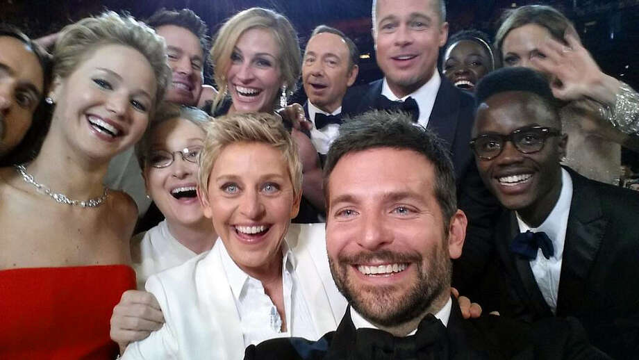 """This image released by Ellen DeGeneres shows actors front row from left, Jared Leto, Jennifer Lawrence, Meryl Streep, Ellen DeGeneres, Bradley Cooper, Peter Nyong'o Jr., and, second row, from left, Channing Tatum, Julia Roberts, Kevin Spacey, Brad Pitt, Lupita Nyong'o and Angelina Jolie as they pose for a """"selfie"""" portrait on a cell phone during the Oscars at the Dolby Theatre on Sunday, March 2, 2014, in Los Angeles. Photo: Ellen DeGeneres, AP / Ellen DeGeneres"""